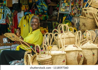 Montego Bay, Jamaica - June 04 2015: Smiling Jamaican female vendor sitting in her stall with woven baskets and other products at a local craft market in Montego Bay, Jamaica.