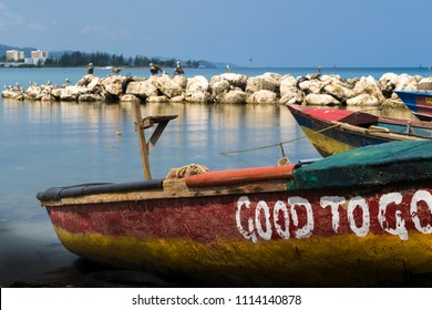 Montego Bay, Jamaica - March 19 2018: Colorful rasta color fishing boats by the seaside and pelicans and other birds on large ocean rock boulders in background.
