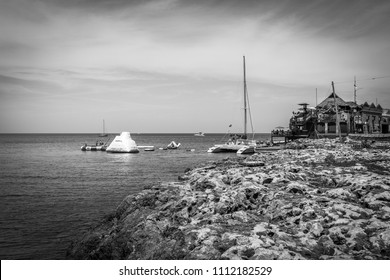 Montego Bay, Jamaica - March 20 2018: Beautiful cliffside ocean view on Caribbean island. Tourists enjoying a sunny summer day on water trampolines and a catamaran at Margaritaville Montego Bay.