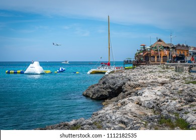 Montego Bay, Jamaica - March 20 2018: Beautiful cliffside ocean on Caribbean island. Tourists on water trampolines and catamaran cruise near Margaritaville Montego Bay. Aircraft landing in background.