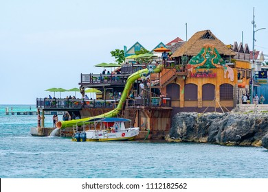 Montego Bay, Jamaica - March 20 2018: People enjoying a sunny day in the Caribbean at Jimmy Buffett's Margaritaville Montego Bay by the cliffs on the ocean.
