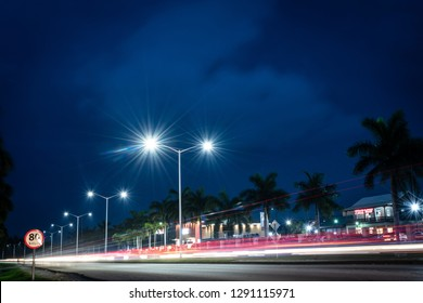Montego Bay, Jamaica - March 20 2018: Nighttime on the street along the Elegant Corridor Highway in Montego Bay with palm trees along the road and the Whitter Village Shopping Mall in the background.
