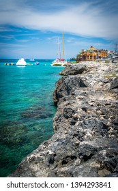 Montego Bay, Jamaica - March 20 2018: Tourists enjoying water trampoline activities on sunny summer day on tropical Caribbean island. Beautiful turquoise ocean along cliff landscape at Margaritaville.