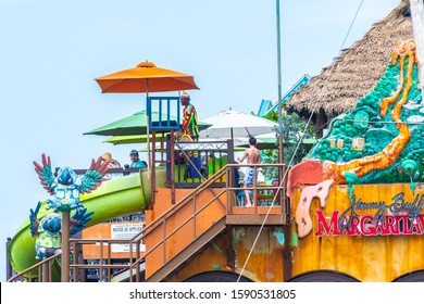 Montego Bay, Jamaica - March 20 2018: Sunny summer day at Margaritaville in the Caribbean. Local Jamaican worker dressed as colorful mascot; caucasian tourists enjoying restaurant & water activities.