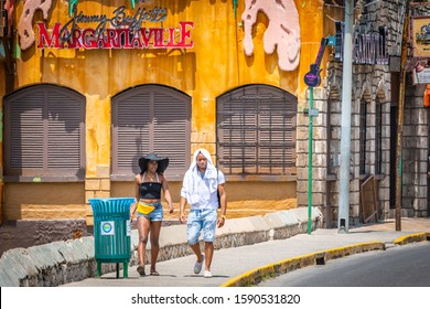 Montego Bay, Jamaica - March 20 2018: Young cute African-American millennial tourists walking by Margaritaville Montego Bay on sunny summer day on the Caribbean island.Male & female couple on vacation