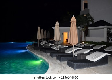 Montego Bay, Jamaica - November 28, 2014: Closed patio umbrellas and lounge chairs by the pool at night inside Secrets Resort, Montego Bay