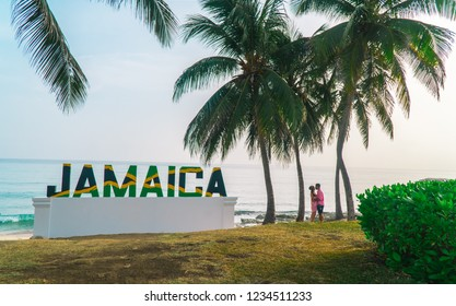 Montego Bay/Jamaica - July 2018: Couple kissing on beach, past a large sign of 'Jamaica' letters in the Jamaican flag, with beach and palm tree background.