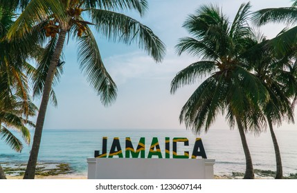 Montego Bay/Jamaica - July 2019: Large sign of 'Jamaica' letters in the Jamaican flag, with beach and palm tree background.