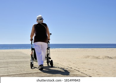 MONTEGORDO, PORTUGAL- FEBRUARY 22, 2014; Old lady with rollator at the beach on a sunny day.February 22, 2014 Montegordo, Portugal