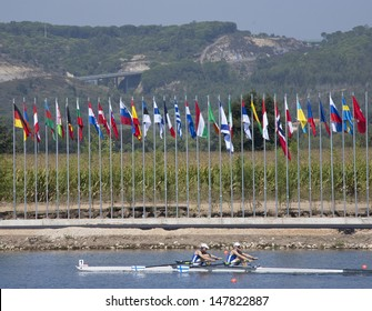 MONTEMOR-O-VELHO, PORTUGAL 11/09/2010. Finnish rowers race past the flags of the competing nations at the 2010 European Rowing Championships held at the Aquatic Centre, Montemor-o-Velho, Portugal.