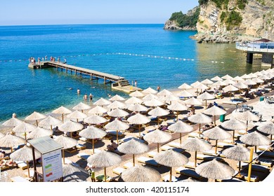 MONTENEGRO, BUDVA - JULY 12, 2015: Tourists on famous Mogren beach near Budva in Montenegro. Sandy beach is located in 150 m away from the old city.