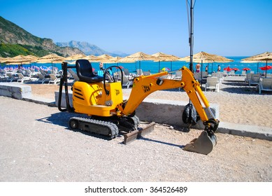 MONTENEGRO, BUDVA - JUNE 2012. Working together on the coast to lay electrical cables for lighting. To do this, they brought a small but powerful yellow an excavator.