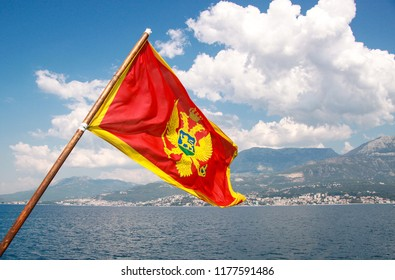 Montenegro flag at Kotor bay. Flag of Montenegro on a background of mountains and Adriatic sea. Space for text.