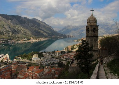 Montenegro, Kotor - APRIL 10, 2018: Top view of a bell tower in the city of Kotor and the bay surrounded by mountains.