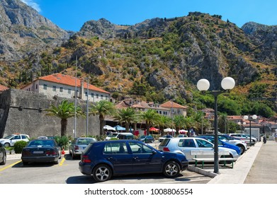 Montenegro, Kotor - August 13, 2017: View to the street along the port of Kotor, in the background are seen fortress walls around Kotor, the length of more than 4.5 km