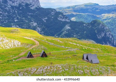 Montenegro, national park Durmitor, houses, mountains and clouds panorama. Sunlight lanscape. Nature travel background