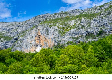 Montenegro, Ostrog monastery building hidden in rock wall cliff, visited by hundreds of thousands pilgrims every year on holy ground surrounded by green trees and forest