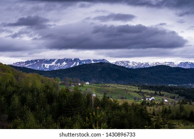 Montenegro, Snow on high mountains of durmitor national park next to zabljak hidden in clouds and surrounded by endless green forest land nature landscape