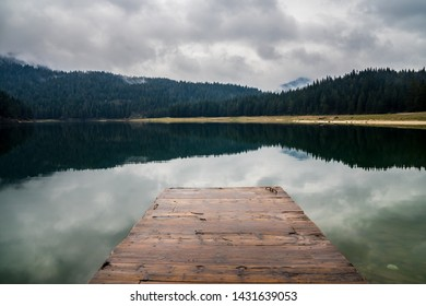 Montenegro, Wooden landing stage in calm waters of black lake surrounded by endless green forest in nature landscape of durmitor national park near zabljak