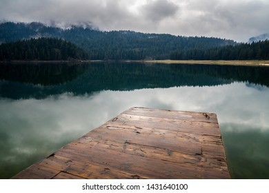 Montenegro, Wooden landing stage in perfect black lake nature landscape surrounded by green forest in misty atmosphere in durmitor national park next to zabljak