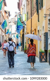 Montepulciano, Italy; 10th May 2018; a Tourist Couple Walking Along a Mediaeval Street in Montepulciano.  Woman Wears Bright Coloured Top and Carries Umbrella.