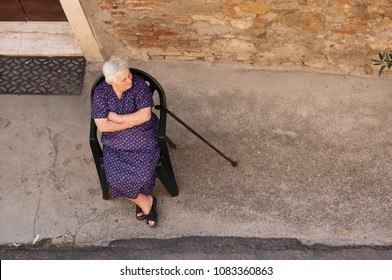 Montepulciano / Italy - august 11 2009: Old italian mad or grumpy lady sitting in chair on the street.