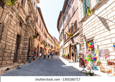 Montepulciano, Italy - August 28, 2018: Narrow alley street in small town village in Tuscany during day on sunny summer day with souvenir shops