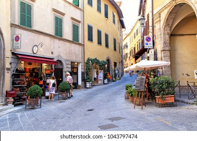 MONTEPULCIANO, ITALY - JULY 19, 2017: Cityscape with tourists, souvenir shops and cafe in the medieval village of Montepulciano, Tuscany, Italy