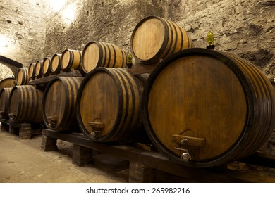 MONTEPULCIANO, ITALY - MAY 16, 2014: Wine barrels stacked in the old cellar of the winery.