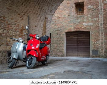 Montepulciano, Italy- October 3 2017: Red and grey vintage Vespa motorbikes parked on the streets of Montepulciano in Tuscana, Italy.