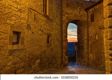 Montepulciano, Italy - view of the sunset through an old arch in a stone wall