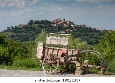 Montepulciano ItalyJune 30th 2015 : Rustic cart advertising local delicacies witjh the hilltop town of Montepulciano in the background