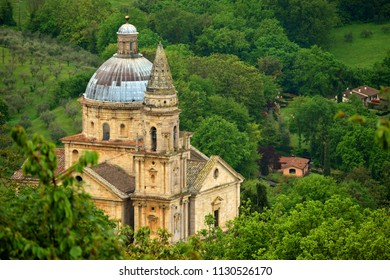 Montepulciano, Tuscany - April 2018. San Biagio is a Renaissance Greek church near Montepulciano, Italy. The church has a blue dome and it is surrounded by the green Tuscan hills.