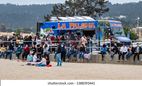 Monterey, California - April 30, 2019: A large group of people wait in line for Mexican food at the La Paloma taco truck, parked on the entrance of  Municipal Wharf 1, at Del Monte Beach.