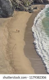 MONTEREY, CALIFORNIA - FEBRUARY 08, 2018: Two people walking along the beach near Brixby Bridger, in California, USA.