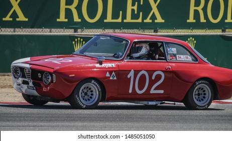 Monterey, California, USA - August 16, 2019: A vintage 1967 Alfa Romeo GTA 1600 Corsa race car rounds a corner in the Rolex Monterey Motorsports Reunion at the WeatherTech Laguna Seca Raceway.