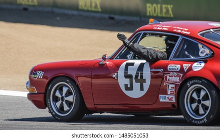 Monterey, California, USA - August 16, 2019: The driver of a vintage 1975 Porsche race car waves to the crowd at the Rolex Monterey Motorsports Reunion at the WeatherTech Laguna Seca Raceway.