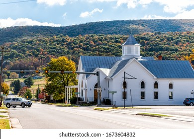 Monterey, USA - October 18, 2019: View of main street road and autumn mountain trees with old architecture church building in appalachia in Highland County, Virginia