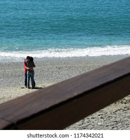 Monterosso al Mare Cinque Terre, Italy  - April 15, 2013 : Young and in love couple hugging with happiness at the beautiful beach of Monterosso ,Cinque Terre, Italy with a wooden rail as foreground.
