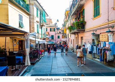 Monterosso Al Mare, Italy - September 02, 2019: People are walking, traveling by a cozy vibrant streets full of small businesses on the ground floor in Monterosso Al Mare, Cinque Terre, Italy