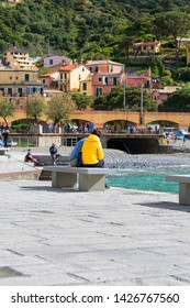 MONTEROSSO, CINQUE TERRE - ITALY, MAY 12, 2019: Typical Italian coastal town, square and colorful houses, people sitting on the bench on the bay of water