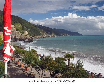 MONTEROSSO, ITALY-SEPT. 22: Tourists walk the tree lined promenade over the  Mediterranean  Monterosso in Cinque Terre, Italy with old town in the distance on the mountain on September 22, 2016.