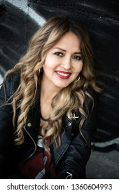 Monterrey Nuevo Leon, Mexico. April 3, 2019. Attractive woman posing in a wall, wearing a black leather jacket.  Forty years old.