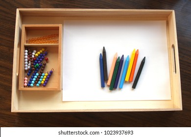 Montessori bead stair on a tray with crayons and a blank piece of paper
