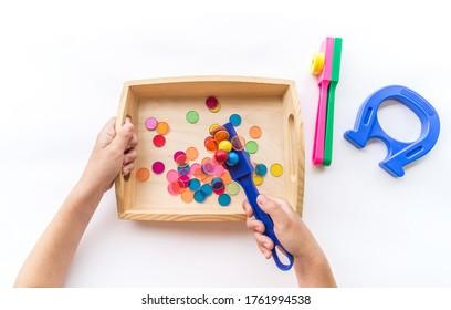 Montessori Magnet Material flach lag. Kinder Hand sortieren. hölzerner Fach auf weißem Hintergrund.