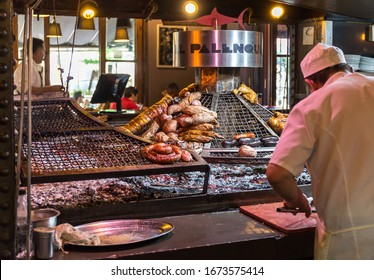 Montevideo , Uruguay- 02/01/2020: A chief in a restaurant in Montevideo Uruguay cooks meat on a wood fire grill.