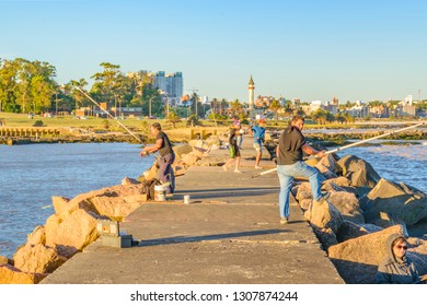 MONTEVIDEO, URUGUAY, DECEMBER - 2018 - Group of people fishing at breakwater in summer day scene at montevideo city, Uruguay