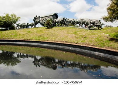 Montevideo, Uruguay, November 16, 2014 - The epic bronze monument on a granite base of a 19th century pioneer wagon and oxen in a city park was created by local sculptor Jose Belloni in 1934