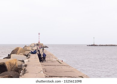 MONTEVIDEO, URUGUAY - SEPTEMBER 2019: People fishing at Escollera Sarandí, next to Montevideo Port