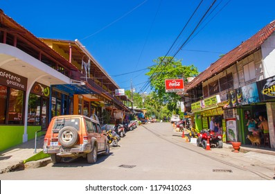 Montezuma, Costa Rica - June 28, 2018: Beautiful view of Montezuma town surrounding of tourists, buildings and and cars parked in the street in gorgeus sunny day in Costa Rica